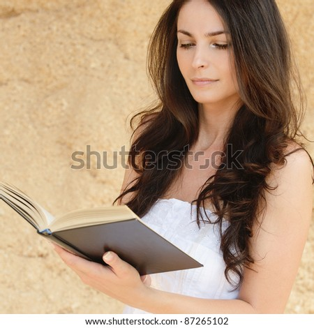 Young attarctive woman reading book against beige background. - stock photo
