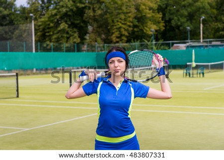 Young attracive woman in sports wear keeps tennis racket on her shoulders at the empty tennis court in summer or spring
