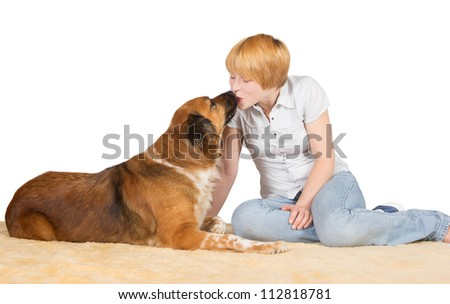 Young attractive affectionate woman sitting on the floor kissing her large gentle dog on the nose with copyspace - stock photo