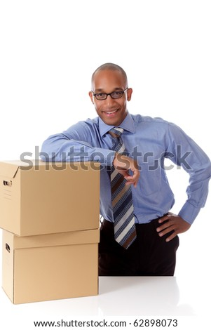 Young attractive African American businessman against the storage boxes with hand on hip . Studio shot. White background. - stock photo