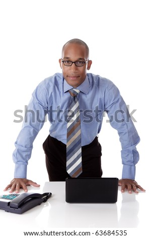 Young attractive African American businessman in office against desk with  laptop and telephone. Studio shot. White background. - stock photo