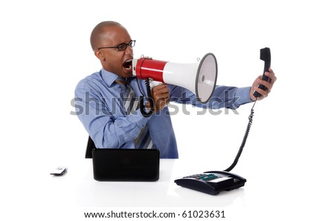 Young attractive African American businessman in office at his desk, yelling angry into megaphone at a telephone receiver . Studio shot. White background. - stock photo