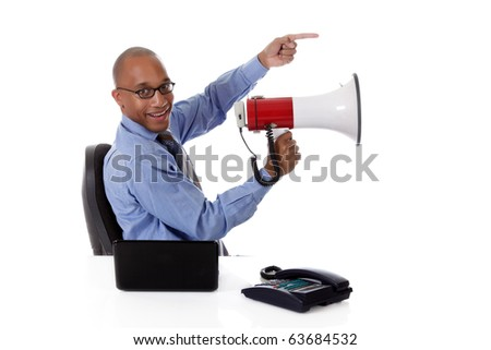Young attractive African American businessman in office sitting at desk with a laptop and telephone, holding a megaphone and pointing . Studio shot. White background. - stock photo
