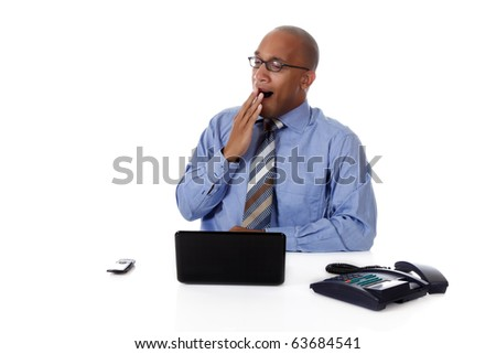 Young attractive African American businessman in office sitting at desk with a laptop and telephone, stifling a yawn. Studio shot. White background. - stock photo