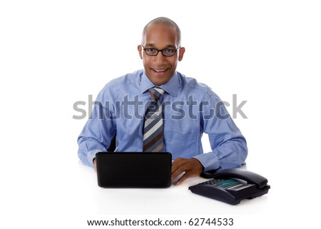 Young attractive African American businessman sitting at his desk with a laptop and telephone. Studio shot. White background. - stock photo