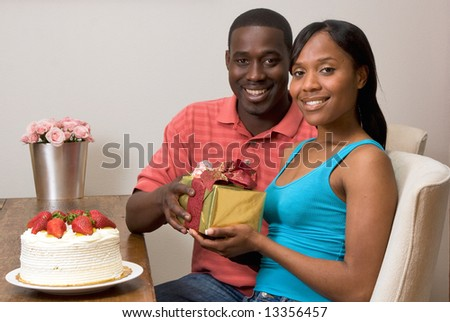 Young attractive african american couple exchanging gifts at their dining table. The couple are smiling at the camera. Horizontally framed shot.