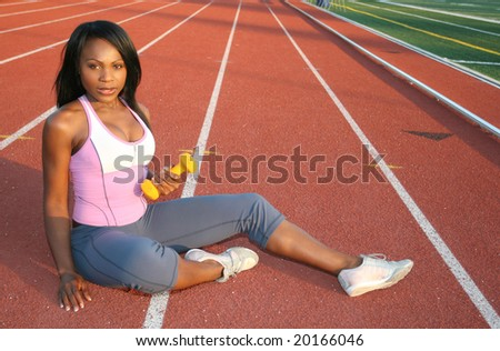 Young attractive African American female working out outdoors at a stadium, track