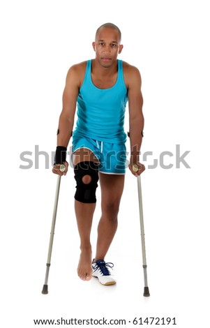 Young attractive African American man athlete on crutches, wearing a wrist brace and knee support,  bandaged. White background. Studio shot. - stock photo