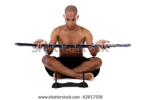 Young attractive African American man sitting cross legged, giving japanese katana sword. Studio shot. White background. - stock photo