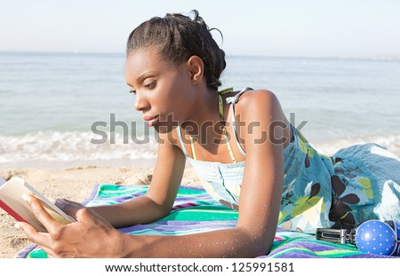 Young attractive african american woman reading a book while laying down on a beach on vacation. - stock photo