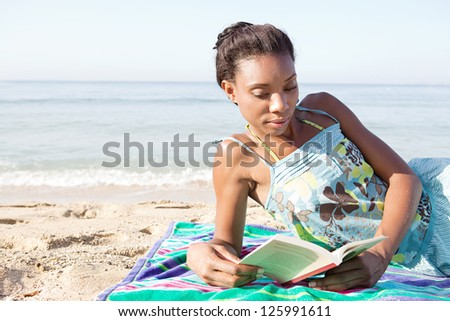 Young attractive african american woman reading a book while laying down on a beach on vacation, relaxing on the shore. - stock photo