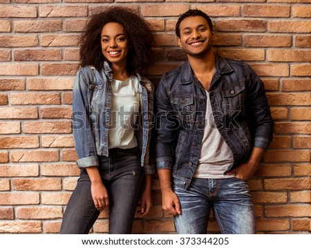 Young attractive Afro-American couple looking in camera and smiling while standing against brick wall - stock photo