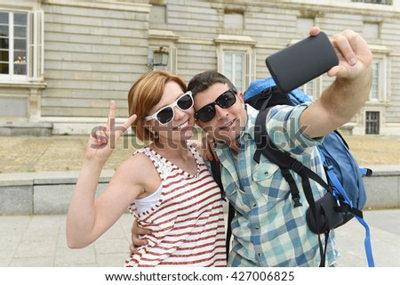 young attractive American couple enjoying holiday trip in Spain taking selfie photo self portrait with mobile phone smiling happy having fun wearing traveler clothes carrying backpack