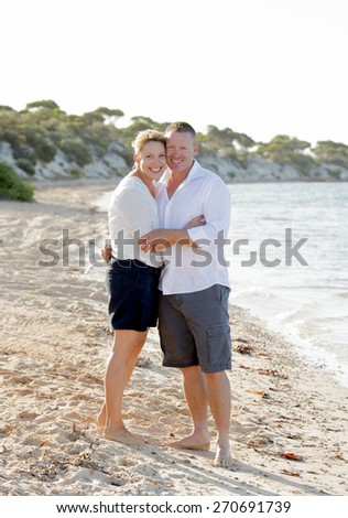 young attractive and beautiful American couple in love walking on the beach the man holding woman with barefoot on the wet sand smiling happy in romantic summer holidays - stock photo