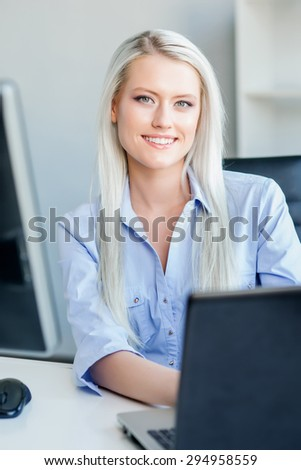 Young, attractive and confident business woman working in office - stock photo