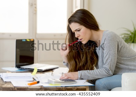 young attractive and desperate woman suffering stress doing domestic accounting paperwork bills and invoices worried and stressed at home sofa couch with laptop computer and bank receipts
