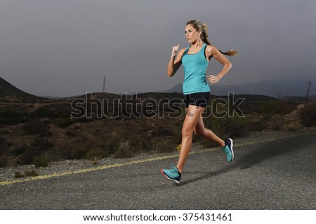 young attractive and fit sport woman running outdoors on asphalt road in mountain landscape on evening with harsh light in fitness workout training shot in motion blurred advertising style - stock photo