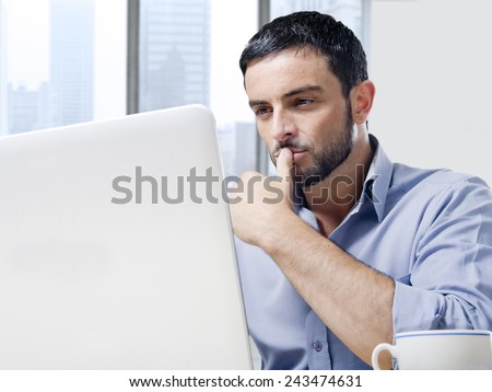 Young attractive and handsome businessman working on computer laptop with coffee cup sitting at office desk in front of skyscraper window view looking concentrated - stock photo