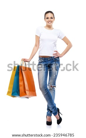 Young, attractive and happy shopping girl with bright shopping bags isolated on white - stock photo