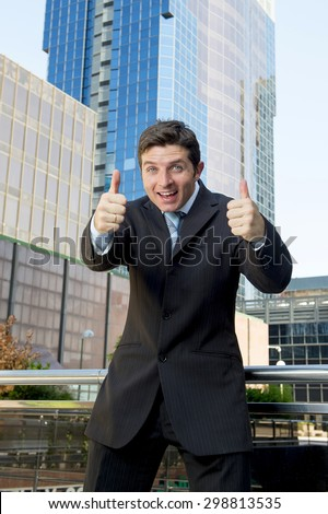 young attractive and successful businessman in suit and tie happy and excited giving thumbs up okay sign after reaching business goal outdoors on financial district - stock photo