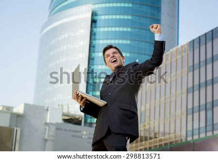 young attractive and successful businessman in suit and tie with computer laptop happy and excited doing victory sign after reaching business goal outdoors in financial district - stock photo