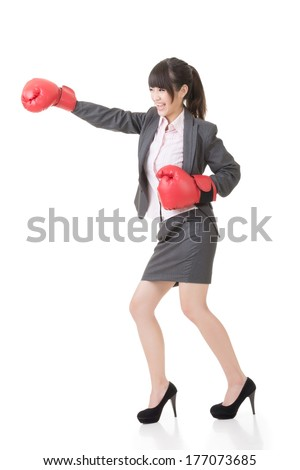Young attractive asian business woman with boxing gloves hit somebody, full length portrait. - stock photo