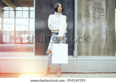 Young attractive Asian girl holding white blank shopping bags in one hand(mock up for paste a logo) - stock photo