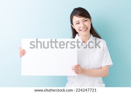 Young attractive asian nurse  holding blank white board - stock photo