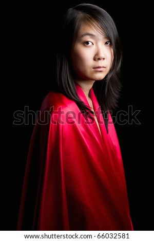 young attractive asian woman in a red gown on a red background - stock photo