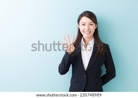 young attractive asian woman indicating the number four - stock photo