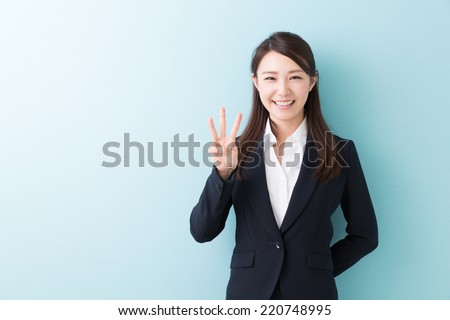 young attractive asian woman indicating the number three - stock photo