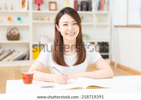 young attractive asian woman keeps household account. - stock photo