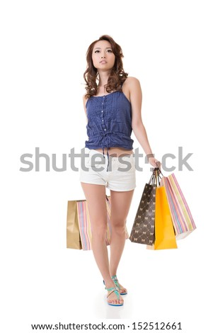 Young attractive asian woman shopping and holding bags. Full length portrait. Isolated on the white background.