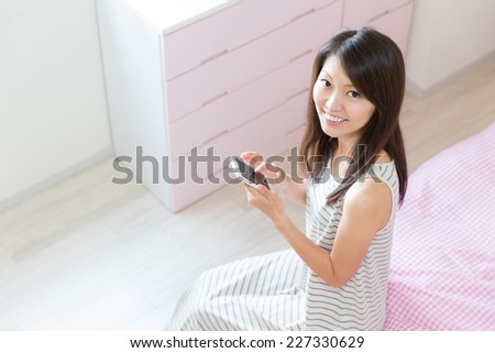 young attractive asian woman  to see a smart phone - stock photo