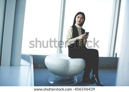 Young attractive asian woman using her cellular phone while is looking out into the skyscraper window of luxury hotel. Female chinese hipster student is using modern contemporary gadget for networking - stock photo