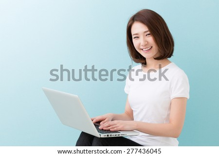 young attractive asian woman using laptop - stock photo