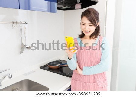 young attractive asian woman who cooks while watching a smart phone in a kitchen - stock photo