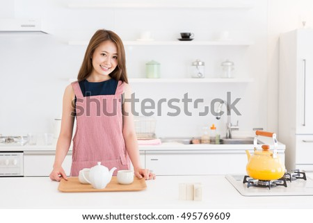 young attractive asian woman who gets ready to drink tea