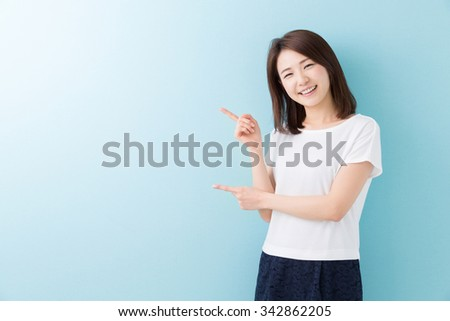 young attractive asian woman who points to the finger - stock photo