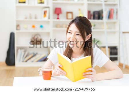 young attractive asian woman who reads a book - stock photo
