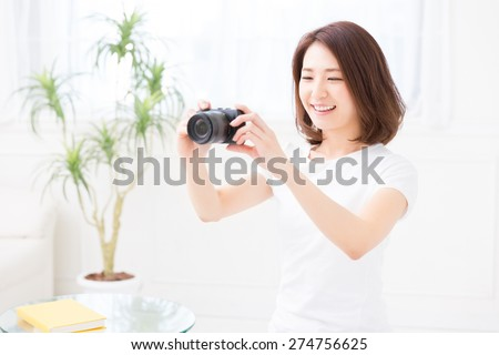 young attractive asian woman who takes a photograph - stock photo