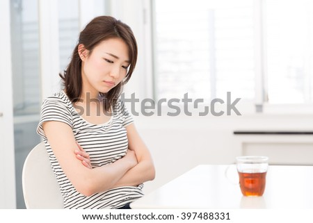 young attractive asian woman who thinks - stock photo