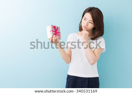 young attractive asian woman who thinks while having a present
