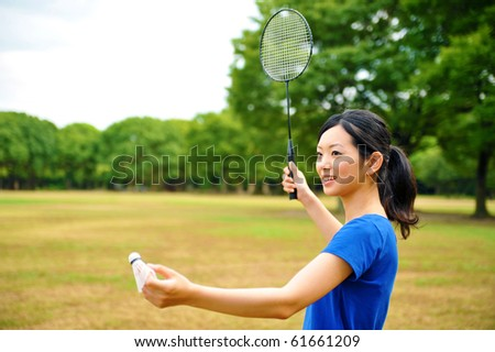 young attractive asian woman with badminton in the park - stock photo