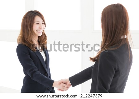 young attractive asian women who shake hands - stock photo