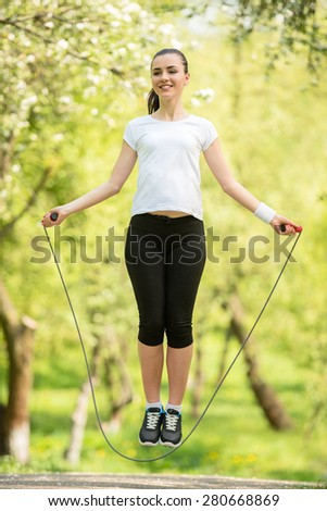 Young attractive athletic girl holding jumping-rope. Workout in the morning outdoors. - stock photo