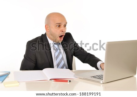 young attractive bald business man sitting at office desk looking at computer reading and watching something that makes him surprised , scared , leaving him in shock - stock photo