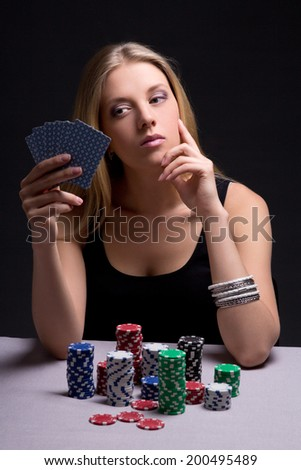 young attractive beautiful serious woman playing poker in casino