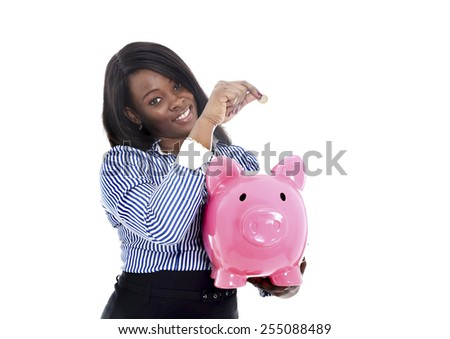 young attractive black African American business woman putting coin into huge and oversized pink piggybank in financial savings concept isolated on white background - stock photo