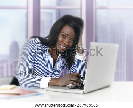 young attractive black African American ethnicity woman working at computer laptop at business district office desk smiling happy in success career concept in pink tinted background - stock photo